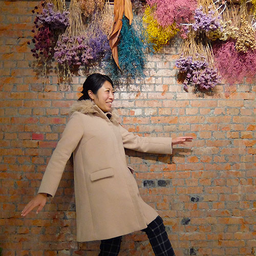 レンガの壁の前に立っている人